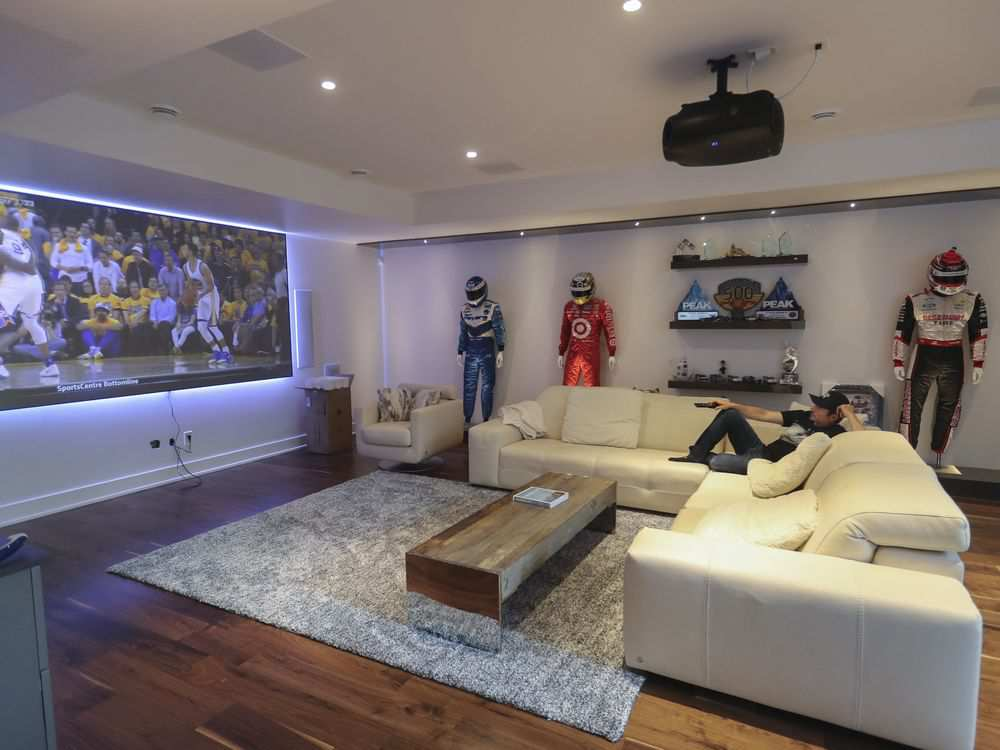 Race car driver Alex Tagliani watches television in his home in Lorraine. The home, which was moved into less than a week ago, is fully decked out with smart devices. (John Kenney / Montreal Gazette)